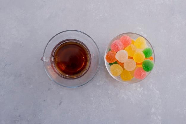 Uma xícara de compotas coloridas com um copo de chá earl grey no centro.