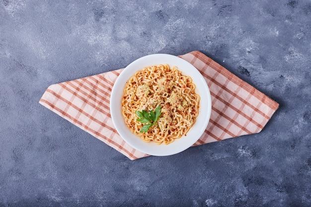 Uma xícara de espaguete com molho de tomate na toalha de cozinha.
