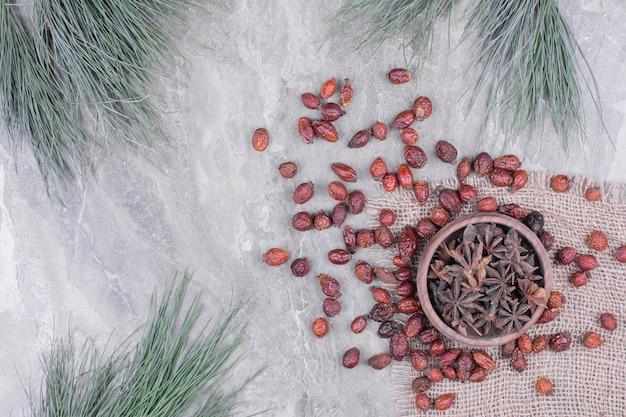 Uma xícara de flores de anis com quadris secos ao redor.