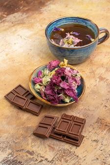 Uma xícara de flores quentes de chá de ervas e barras de chocolate na mesa de cores misturadas