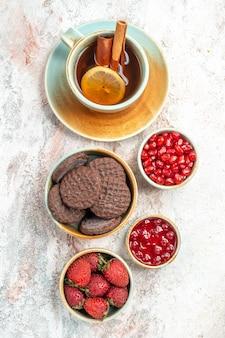 Uma xícara de geléia de chá de romã uma xícara de chá com biscoitos de chocolate com limão