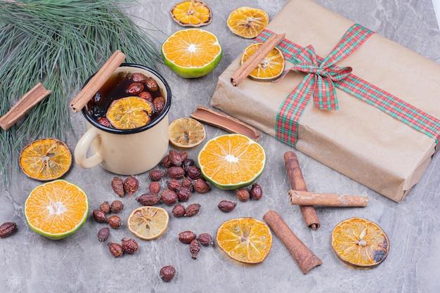 Uma xícara de glintwine com laranja, quadris e canela