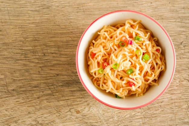 Uma xícara de macarrão instantâneo, colocado sobre uma mesa de madeira com pimenta como ingredientes, macarrão de vista superior e copyspace