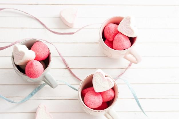 Uma xícara de marshmallows em forma de coração e doce para dia dos namorados, barra de chocolate, festa de menina