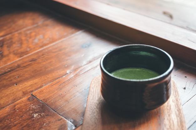 Uma xícara de matcha quente com leite no chão de madeira