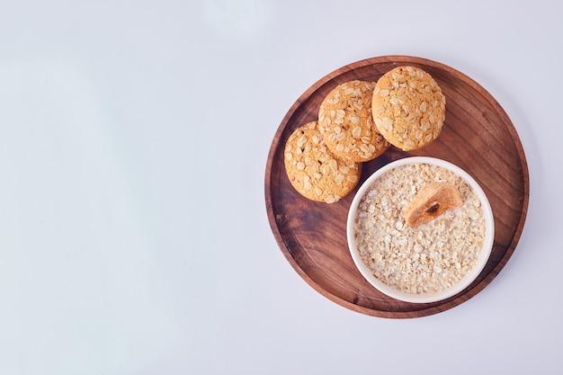 Uma xícara de mingau com biscoitos de aveia, vista superior.