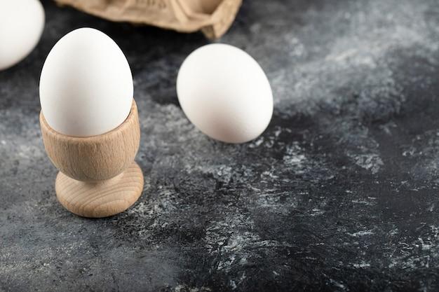 Uma xícara de ovo de madeira com ovo de galinha cozido.