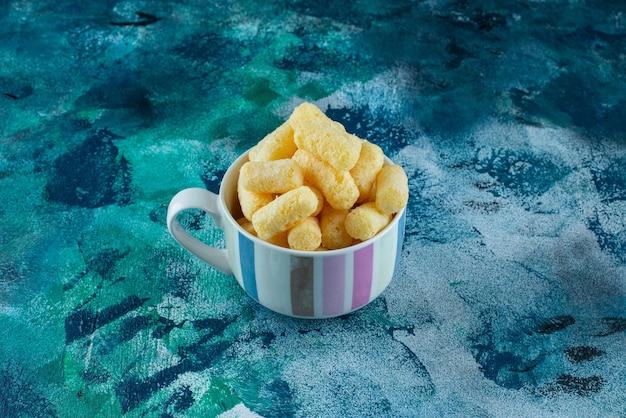 Uma xícara de palitos de milho doce, na mesa azul.