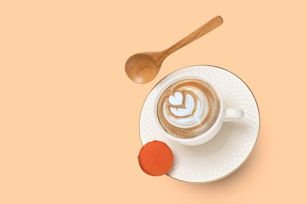 Uma xícara de porcelana branca com cappuccino levitando sobre um fundo de superfície laranja suave