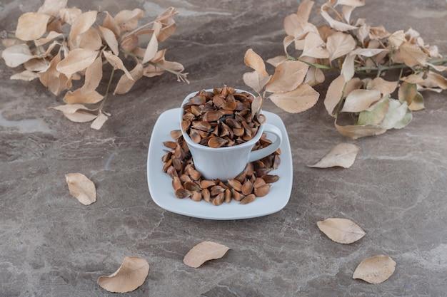 Uma xícara de sementes na frente das folhas na superfície do mármore