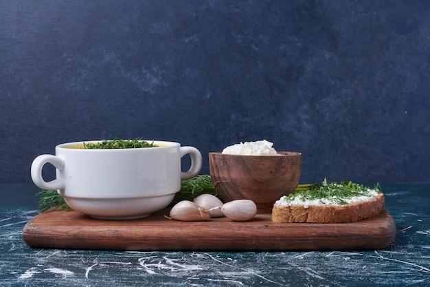Uma xícara de sopa com pão torrado.