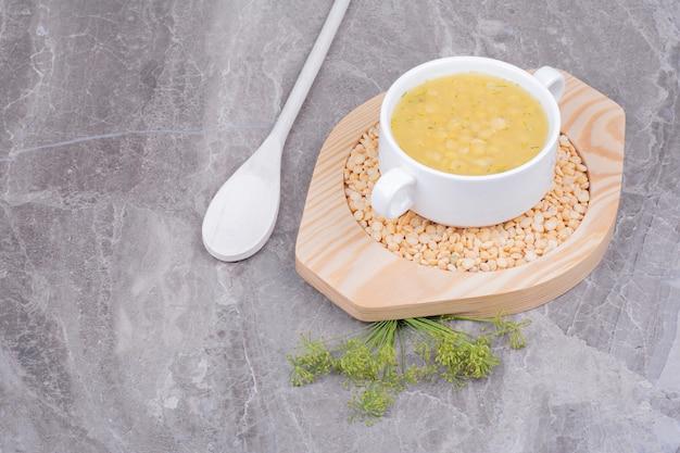 Uma xícara de sopa de feijão de ervilha em feijão cru em uma bandeja de madeira.