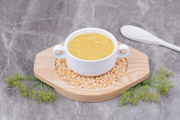 Uma xícara de sopa de feijão em uma travessa de madeira