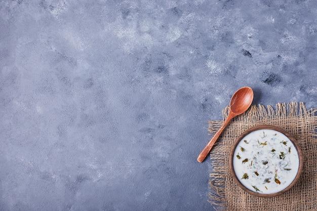 Uma xícara de sopa de iogurte em um pedaço de serapilheira.