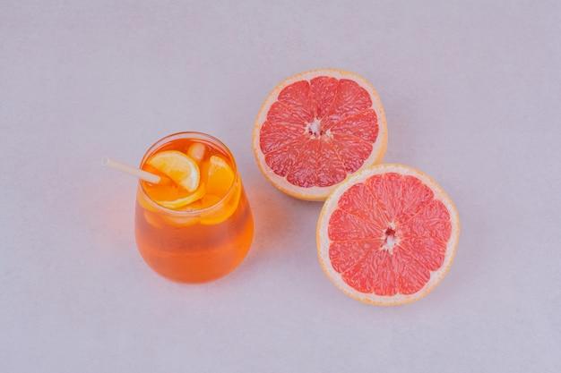 Uma xícara de suco com frutas cítricas dentro