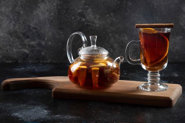 Uma xícara de vidro com chá e paus de canela.