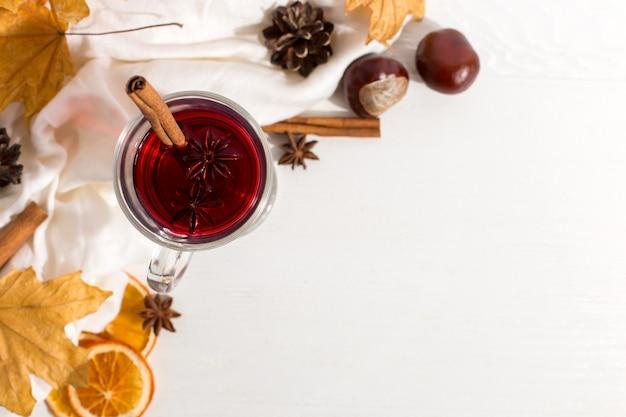 Uma xícara de vinho quente com especiarias, cachecol, especiarias, folhas secas e laranjas em cima da mesa. clima de outono, um método para se aquecer no frio, copyspace.