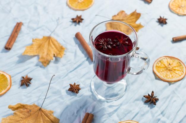 Uma xícara de vinho quente com especiarias, folhas secas e laranjas em cima da mesa. clima de outono, um método para se aquecer no frio, copyspace, luz da manhã.