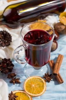 Uma xícara de vinho quente com especiarias, garrafa, folhas secas e laranjas na mesa. humor de outono, método para se aquecer no frio, copyspace, luz da manhã.
