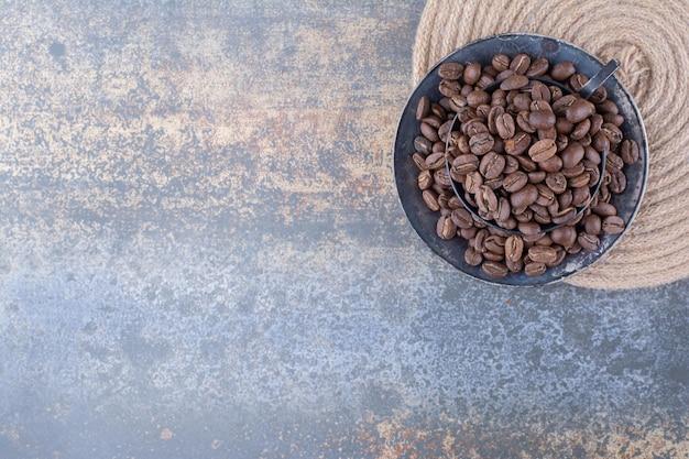 Uma xícara escura cheia de grãos de café em mármore