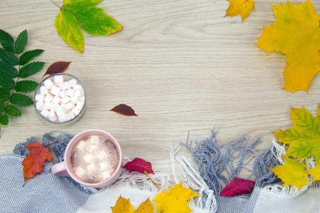Uma xícara grande de chocolate quente com marshmallows e um cobertor quente no fundo de uma velha madeira