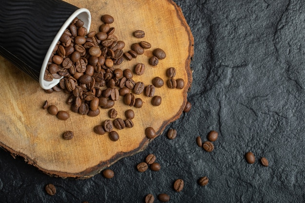 Uma xícara preta cheia de grãos de café na placa de madeira.