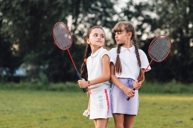 Uma zangada meninas segurando badminton na mão olhando uns aos outros