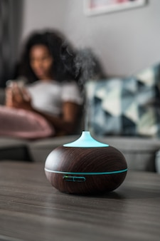 Umidificador de ar inteligente emitindo vapor d'água na mesa perto do sofá com uma mulher negra em casa