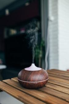 Umidificador inteligente contemporâneo na mesa emitindo vapor de água