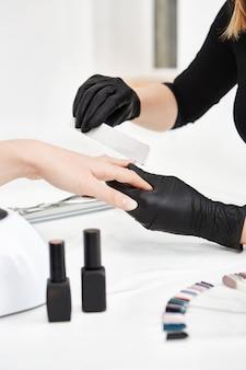 Unha artista encurtando as unhas fazendo manicure no salão. conjunto de manicure.