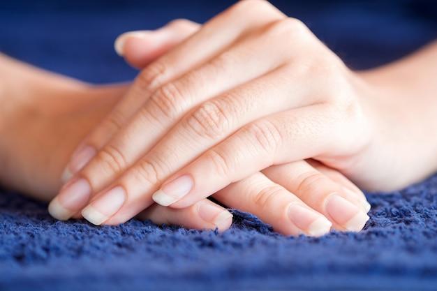 Unha de close-up de mulheres na toalha azul, conceito de cuidados de saúde da unha.