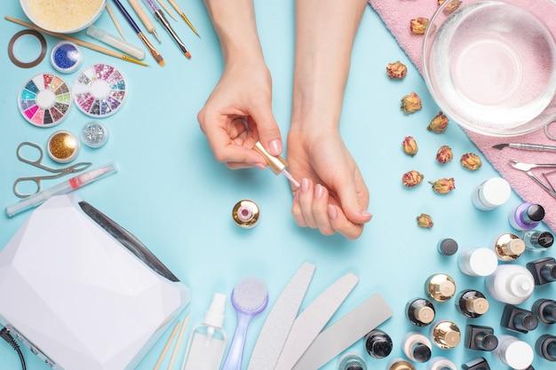 Unhas belamente manicured na área de trabalho com ferramentas para manicure. cuidado com as unhas