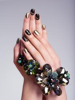 Unhas bonitas de mulher com manicure e joias criativas