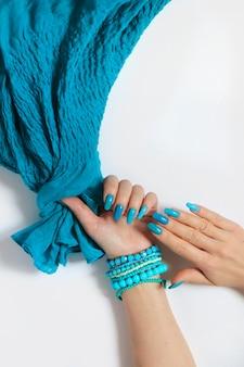 Unhas compridas ovais elegantes com diferentes tons de esmalte de azul claro a turquesa.