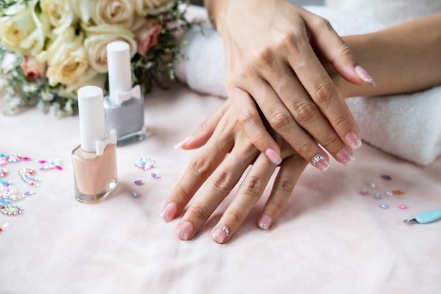 Unhas de manicure bonita pintar com glitter, pedras preciosas e verniz no salão de beleza