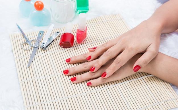 Unhas de mulher bonita manicured com esmalte vermelho