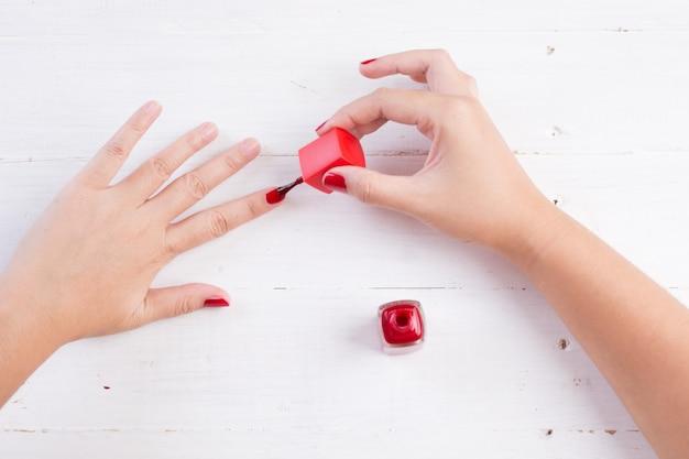 Unhas de mulher com esmalte vermelho