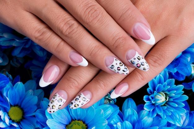 Unhas de mulher lindas com manicure francesa e design de arte