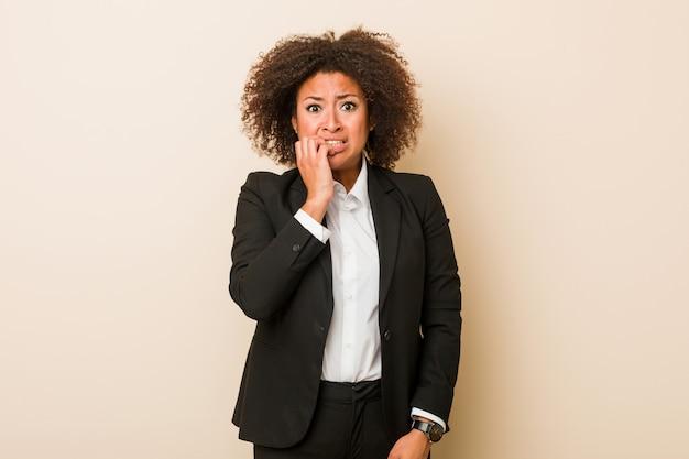 Unhas de roer mulher afro-americana de negócios jovem, nervoso e muito ansioso.