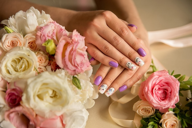 Unhas naturais com bela manicure com flores em flor nas unhas das mulheres perto de buquê de flores frescas