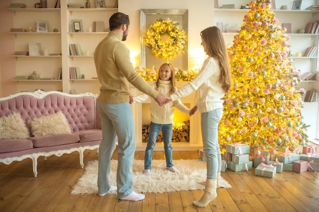 União. família feliz perto da árvore de natal de mãos dadas