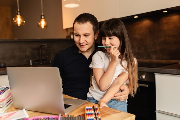 União familiar e aprendizado on-line. pai e filha fazem aula on-line com o laptop em casa