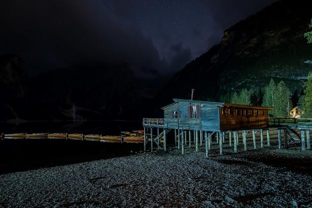 Única cabana de madeira perto do lago braies, na itália, cercada por altas montanhas durante a noite