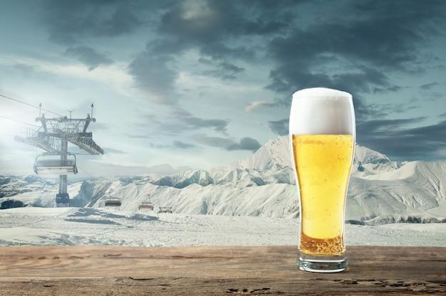 Única cerveja light em vidro e paisagem de montanhas no fundo. bebida de álcool e aparência de neve e céu nublado na frente dele. quente no dia de inverno, feriados, viagens, tempo de aventura.