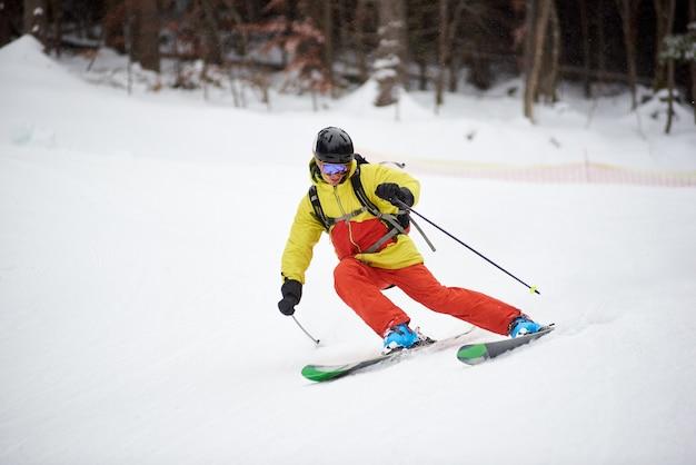 Única descida do jovem esquiador masculino, esqui downhill e fazendo carve virar na encosta alta arborizada. esquiar durante a queda de neve