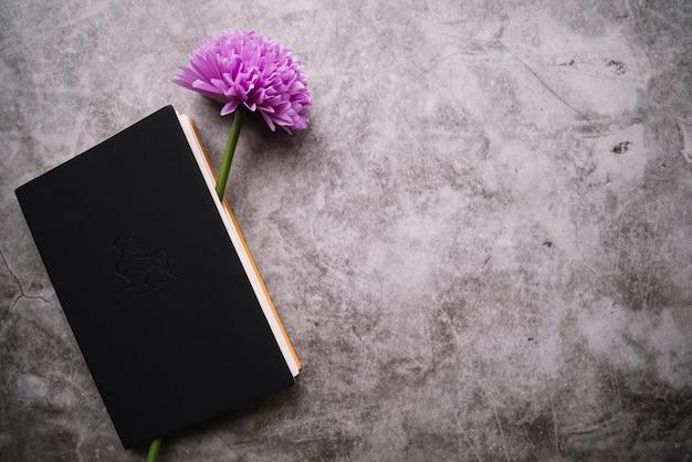 Única flor roxa falsa dentro do caderno fechado no fundo manchado