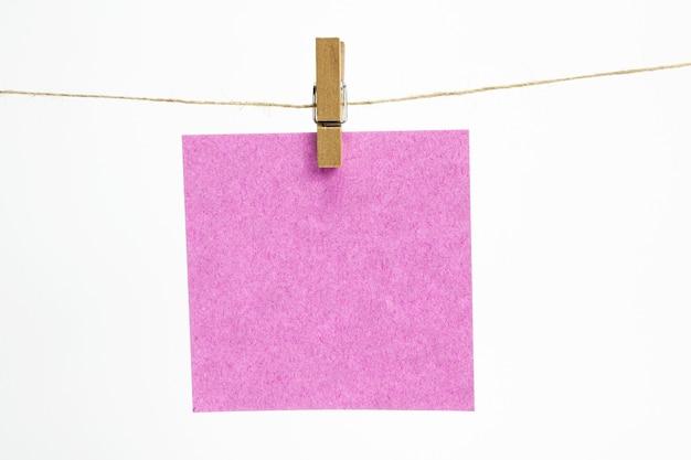 Única folha de papel vazia para notas que penduram em uma corda com prendedores de roupa e isoladas no branco.
