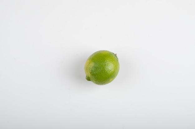 Única fruta limão madura isolada na mesa branca.