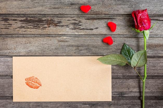 Única rosa vermelha com envelope artesanal com beijo e pequenos corações, em fundo de madeira marrom, vista superior, conceito de dia dos namorados