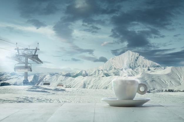 Única xícara de chá ou café e paisagem de montanhas no fundo. xícara de bebida quente com aparência de neve e céu nublado na frente dela. quente no dia de inverno, feriados, viagens, ano novo e época do natal.